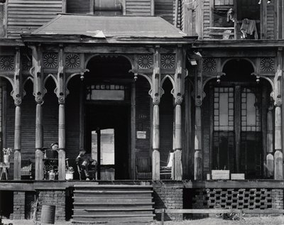 two men seated in chairs on the large porch of an old, slightly run-down Victorian house; woman in window, URC