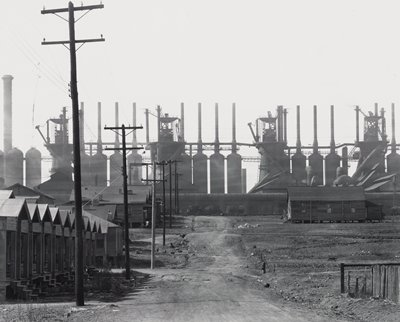 view down a dirt road to a factory; row of small houses and telephone poles down left side of road