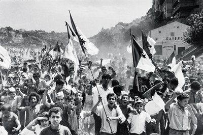 crowd of children and young men, waving flags; buildings in background and at R in middle ground