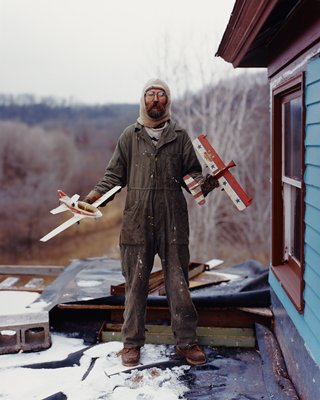 bearded man wearing coveralls, holding a model plane in each hand; house at right