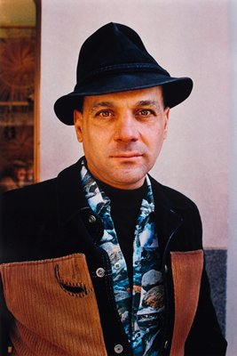 man wearing hat and shirt printed with images of rocks and water; dark jacket with brown panels