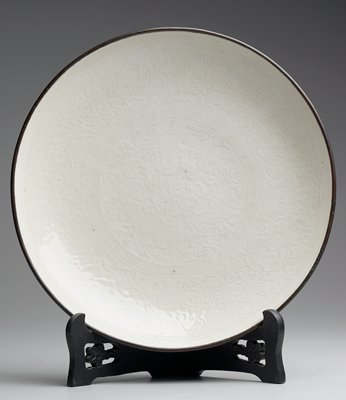 Pai-Ting-yao Plate shallow circular form; light porcellaneous ware, covered with creamy white glaze; inner surface decorated beneath the glaze with floral design in slight relief; rim mounted with copper band.