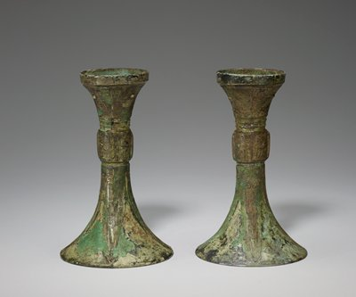 tall thin vessel with a flaring top; round base with four blade shape designs up the sides
