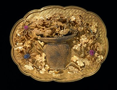 Gold presentation box, cartouche-shaped, scalloped; surface chased with swastika-fret design. Bears the emblem of Lan Tsai-Ho, a basket of flowers, which trail over the cover. One of a set of 8 presented to Emperor Ch'ien Lung in the 43rd year of his reign.
