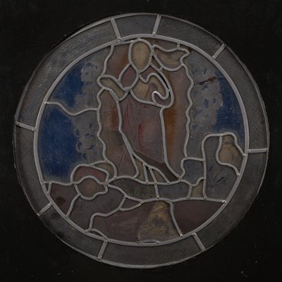 round stained glass panel depicting the Resurrection, with a standing Jesus with two figures at bottom--one sleeping, the other startled; hand-drawn grid and circle patterned border