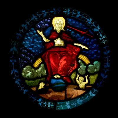 round stained glass panel depicting Christ enthroned with two figures beneath him; floral border