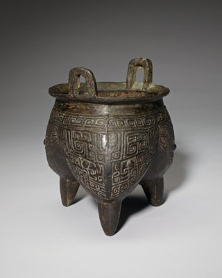 3 bulbous sections at bottom with 3 thin legs; 2 u-shaped handles; incised geometric designs on exterior bulbous sections