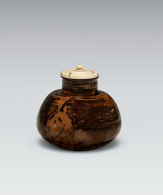 squat tea container with short, upright neck; dark brown glaze with areas of tan and yellowish tinting; incised horizontal line; small ivory cover with small knob