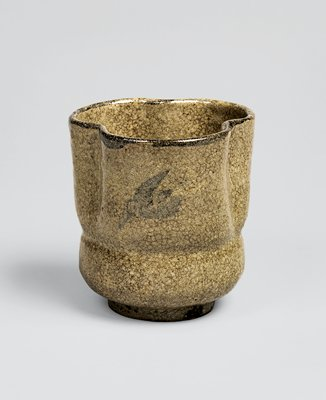 cup with three lobes; beige in color with underglaze design of diving birds in darker color; darker glaze around lip; incised line below lobes where cup rounds out to bottom