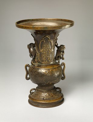 flower vase with squat, round body, high neck, and high foot; ornately decorated with figures in relief; figure of a sage and a crane on each side of neck; two handles
