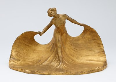 striding woman, leaning forward, wearing a very long low-cut strapless dress with its skirts pooling around her feet; woman holds the hem of her dress in each hand; gold patina