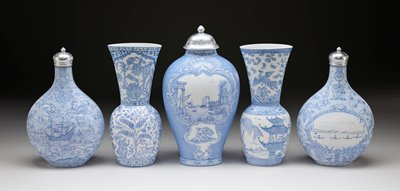 oval concave base; sides flare outward slightly from base then steeply inward about halfway up body of vessel, then slightly outward again along tall neck to wide oval mouth opening; white porcelain with light blue designs; decorated on one side with a pair of figures, pair of deer and figure with sword on horseback slaying a large cat surrounded by floral and foliage motifs at bottom and bird with large flowers at top; opposite side decorated with blooming plant at bottom and pair of figures--one seated, one standing--and pair of peacocks flaking a dancer on a stool with a horn at top; floral bands at top, bottom and shoulder