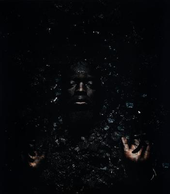 photograph of darkened, non-descript background; the face of a bearded black man emerges in middle center; PR and PL hands also emerge in LLC and LRC; scattered bits of dirt surrounds face and hands
