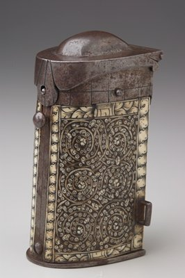 mailbox shaped box with hinged lid; slots for 4 cartridges inside; carved and inlaid bone in wood spiraling decoration on both sides; release button for lid on front; ring for hanging on each side; wood rectangle surrounded by bone on back; steel lid and bottom.