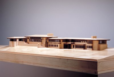 model of Frank Lloyd Wright designed house; 3 short flights up a small hill on one long side; semicircular porch on same side; large, sprawling floor plan