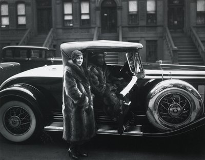 woman in raccoon coat beside car; man seated inside car