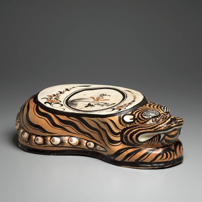 ceramic pillow shaped like a reclining tiger with tail against PR side of body; flat top section decorated with floral designs and insect; brown and orange glaze