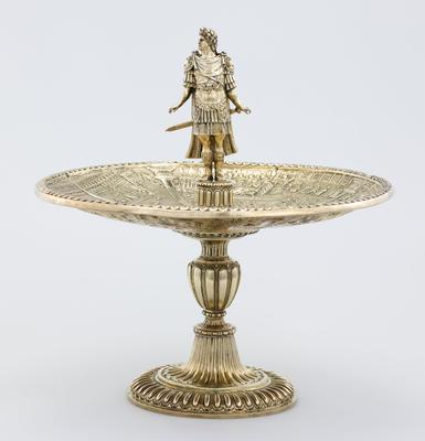 silver gilt, separates into five parts; fluted foot and bowl with four panels embossed with scenes of the life of the emperor Caligula and capped with a cast and chased figure of Emperor Augustus