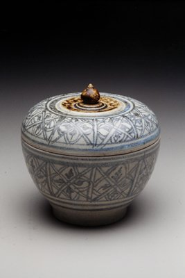 covered bowl panels of geometric designs on both bowl and cover; footed bowl, pointed finial on cover; pale blue and brown glazes