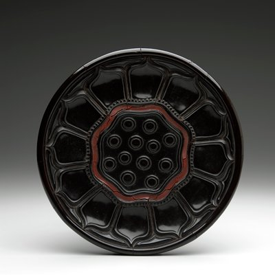 brownish black dish; top carved in the design of a lotus flower with seeds in the center, the pod outlined in red; underside carved in Guri design (scroll pattern around edge)