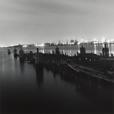 ruined dock in forground; shipyard in background with lights