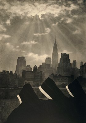 """three nuns in habits in foreground with city skyline in background under """"heavenly"""" light"""