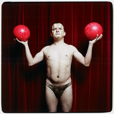 man wearing small leopard-print bikini pants, with Band-Aids on his face, holding a pink bowling ball in each hand; man stands in front of a dark red curtain