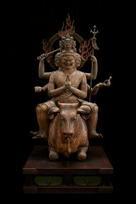 """figure with six heads, arms, and legs astride crouched bull on wood base; metal bands around wrists, some biceps, and most ankles; halo with flames attached at back; two hands of two arms together in praying position, other arms bent and flare outwards. Upper left arm holds long staff, lower one holds implement with """"curly q""""-shaped end. Upper right arm holds a trident. Lower right arm fingersshaped like it was holding something in hand. Three bottom heads have crystal inlay eyes. Three smaller heads on top considerably smaller."""