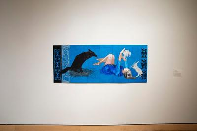 a: bright blue ground with black and white appliques running vertically up the L side; image of a black coyote seated in a bird-like nest licking a pair of feet along the R side of the image b: bright blue ground with black applique filigree along the R edge; woman lying on her back in a blue dress holding a white rabbit above her head; a second white rabbit hops to the right of her head