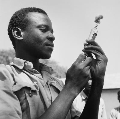 Black and white image of a man holding a syringe