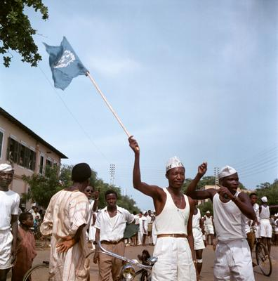 Color image of a group of men wearing mostly white, one of which is waving a light blue UN flag