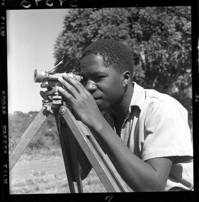 Black and white image of a man using a telescope on a tripod