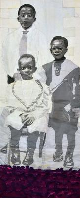 black and white image of three young Black children, two are standing and the youngest is seated; rows of dimensional flowers in pink and purple below their feet