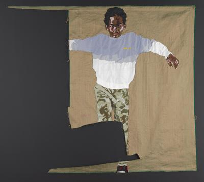 irregularly shaped textile with a green/gold metallic ground; image of a young Black boy in camouflage pants and a sweatshirt that is white on the bottom and light blue on the top; figure has his arms outstretched and he is looking directly at the viewer; the PR side of the textile/image is cut away at the boy's wrist and into his legs; thin rod pocket on verso along top edge