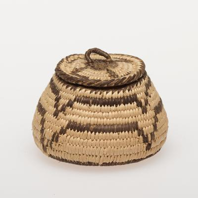 Miniature olla basket with cover; coiled. Design consists of a double row of zig-zag stripes around the body of the basket. Cover has a swastika. Colors are natural and black.