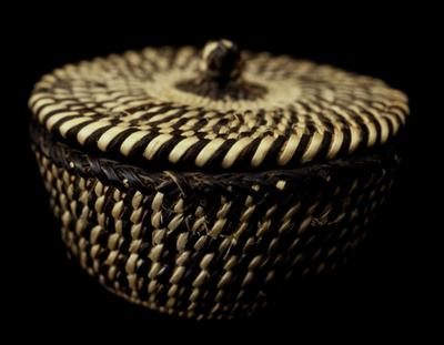 Miniature round basket with attached cover; coiled. Design consists of vertical stripes in natural and black.