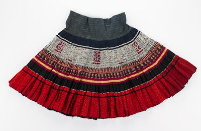 wrap-around style with two ties; blue striped waist; densely-pleated skirt with batik panel embellished with purple and yellow embroidery; black woven band below; red woven design on bottom hem