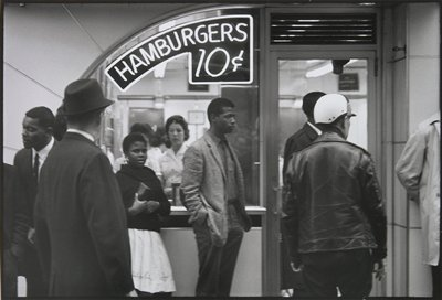 """seven figures, including one girl, standing in front of a window with a neon sign reading """"HAMBURGERS 10¢"""""""
