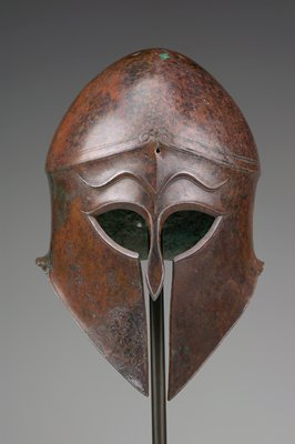 face-covering helmet with back and sides curled upward; vertical opening at center from eye holes through bottom; organic design on forehead; curving eyebrows, connected at center