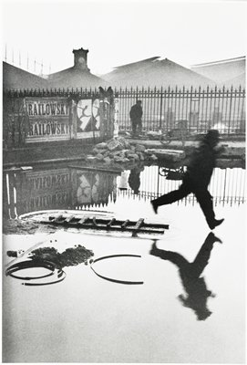 man running through flooded area, his reflection is shown in the water