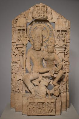 husband and wife seated on a lotus in the pose of royal ease and intimacy with bull and tiger underfoot; symmetrical architectural backdrop with large central disc behind heads of main figures