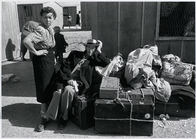 black and white photograph of man wearing hat and coat seated on suitcase next to woman standing with hand on her hip