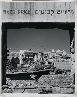 """bombed buildings and rubble seen through an opening with a sign """"Fixed Price"""" above"""
