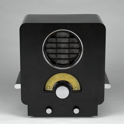 rectangular body with rounded corners on a slightly smaller base; round speaker with yellow dial below; three chrome knobs and chrome accented handles