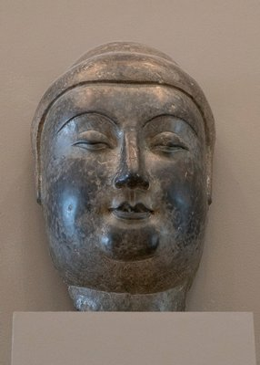 Stone head of Buddha. A fragment consisting of the face only, modelled in the style that heralds the Tang.
