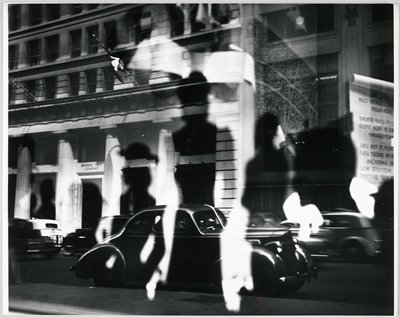 window reflection of a building (Bankers Trust Company) with a collonade, frieze and flags; 1940's era cars parked along street; shadows of figures