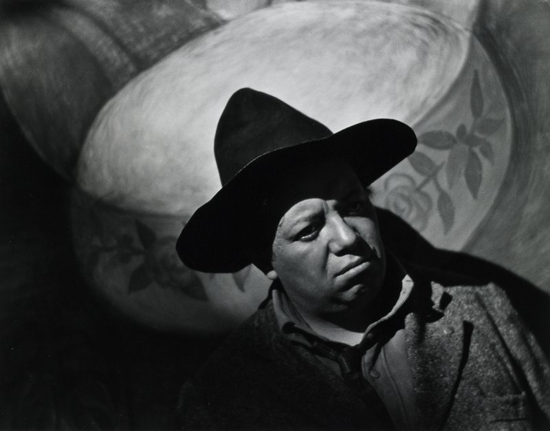 portrait of Diego Rivera, wearing a hat, in front of a mural with image of a large bowl behind his head; figure on a diagonal from LRC