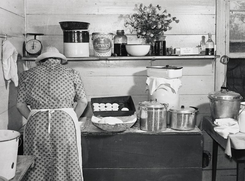 woman wearing a plaid dress, apron and hat at left, seen from back; pan of biscuits and ball of dough at center of counter, with various pots, pans and utensils on counter, table and right and shelf above counter