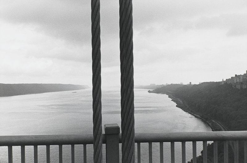 foreground railing and cables of bridge; looking out over river; buildings on hill at right