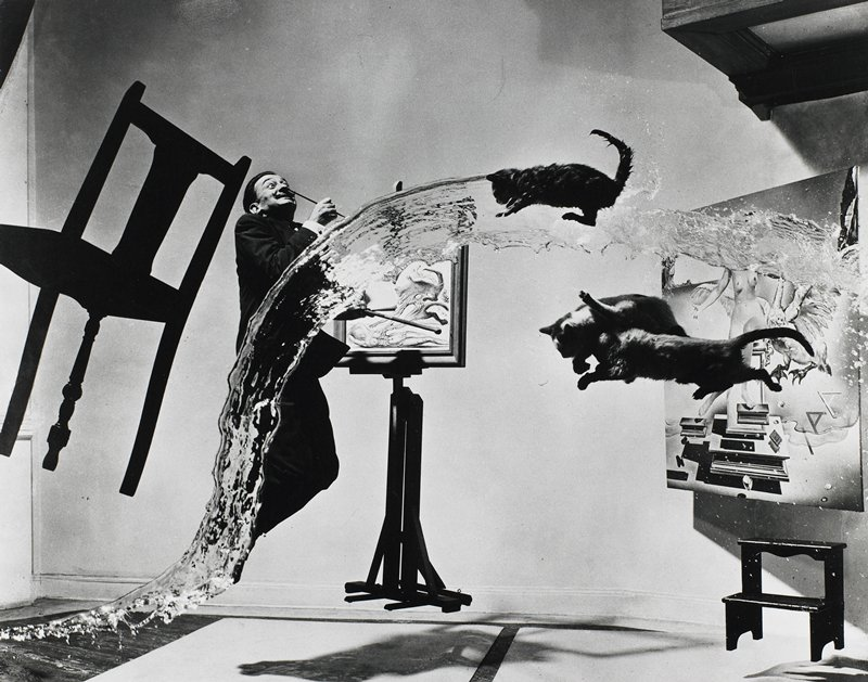 Salvador Dali jumping, standing before an easel elevated off the floor; levitated painting and stool at right, chair at left; 3 jumping cats at right; long water splash in foreground